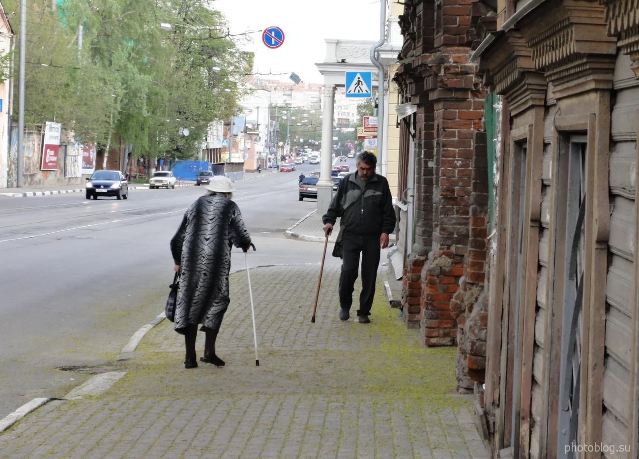 Старики с клюкой идут навстречу друг другу. На тихой улице